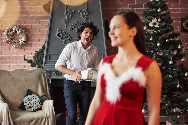 Dziewczyna odwróci się i zobaczy faceta stojącego z prezentem za sobą. kobieta w czerwonej sukience otrzyma teraz prezent świąteczny od chłopaka.