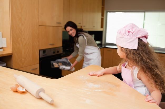 Dziewczyna ogląda jej macierzystych kładzenia ciastka w piekarnika