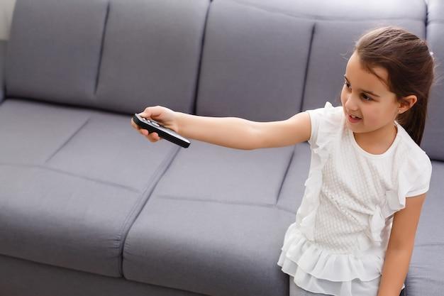 Dziewczyna Ogląda Telewizję, Pilot Zdalnego Sterowania Premium Zdjęcia