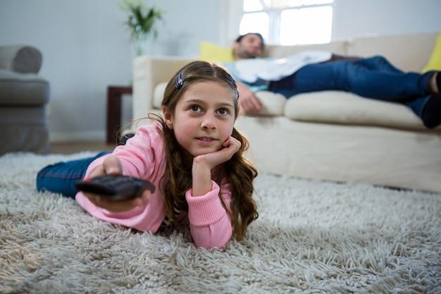 Dziewczyna ogląda tv kłama na dywaniku w żywym pokoju