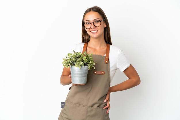 Dziewczyna ogrodniczka trzymająca roślinę na białym tle, pozująca z rękami na biodrach i uśmiechnięta
