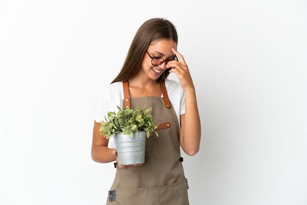 Dziewczyna ogrodniczka trzymająca roślinę na białym tle, śmiejąca się