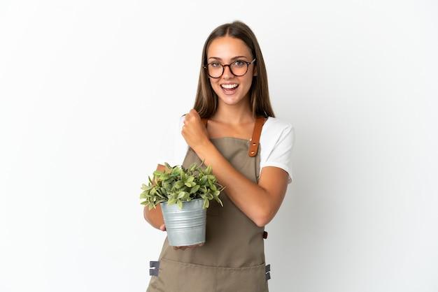 Dziewczyna ogrodniczka trzymająca roślinę na białym tle świętująca zwycięstwo