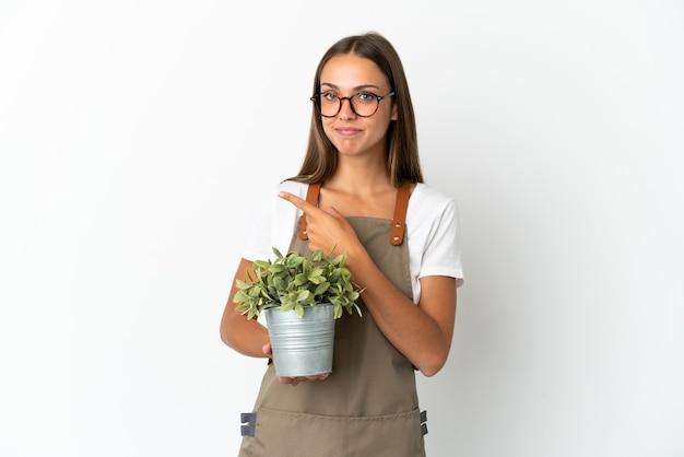 Dziewczyna ogrodniczka trzymająca roślinę na białym tle, wskazująca na bok, aby zaprezentować produkt