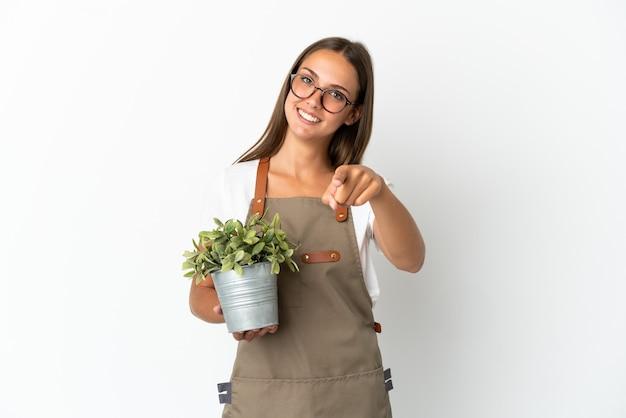 Dziewczyna ogrodniczka trzymająca roślinę na białym tle, wskazująca przód ze szczęśliwym wyrazem twarzy