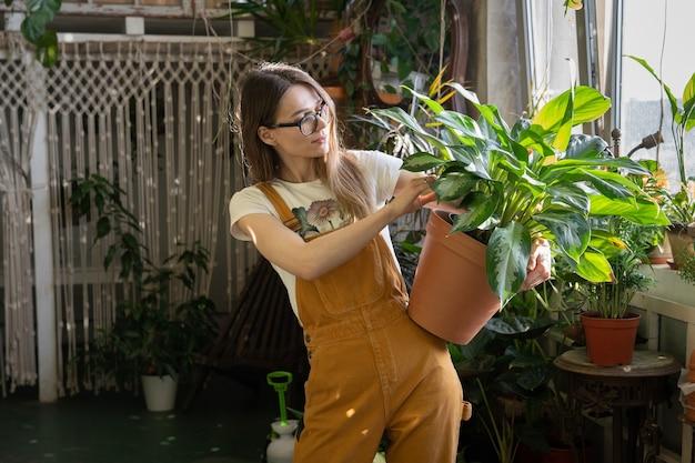 Dziewczyna ogrodniczka z doniczką w kombinezonie pracuje w przydomowym ogrodzie