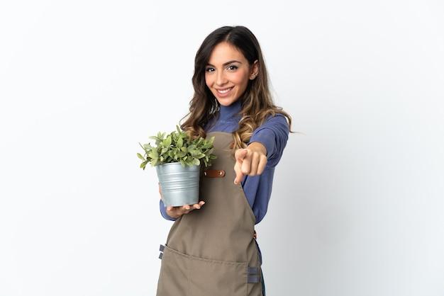 Dziewczyna ogrodnik gospodarstwa roślin na białym tle na białej ścianie, wskazując przód z happy wypowiedzi