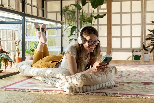 Dziewczyna ogrodnik relaksuje się po pracy na wiadomości podłogowej na smartfonie i słucha muzyki relaksacyjnej w domu
