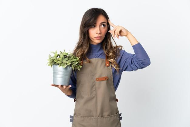 Dziewczyna ogrodnik trzyma roślinę na białym tle na białej ścianie, mając wątpliwości i myśli