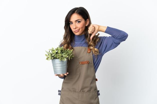 Dziewczyna ogrodnik trzyma roślinę na białym tle na białej ścianie pokazuje kciuk w dół z negatywnym wyrazem