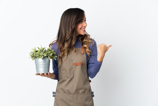 Dziewczyna ogrodnik trzyma roślinę na białym tle na białej ścianie, wskazując w bok, aby przedstawić produkt