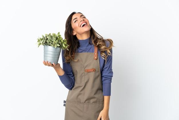 Dziewczyna ogrodnik trzymając roślinę na białym tle na białej ścianie, śmiejąc się