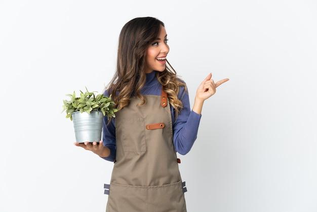 Dziewczyna ogrodnik trzymająca roślinę na białej ścianie, zamierzająca wykonać rozwiązanie, podnosząc palec w górę
