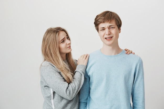 Dziewczyna okazuje współczucie. siostra pocieszająca brat, który czuje się przygnębiony