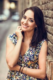 Dziewczyna ono uśmiecha się na ściana z cegieł z niebieskimi oczami.