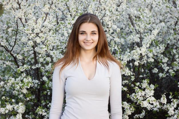 Dziewczyna ono uśmiecha się na tle kwiatonośny drzewo.