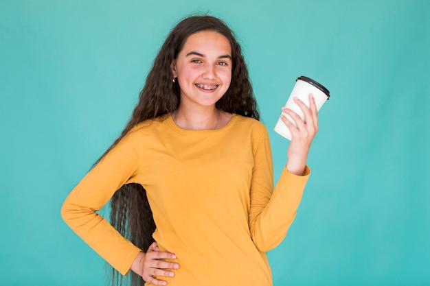 Dziewczyna ono uśmiecha się podczas gdy trzymający jej napój