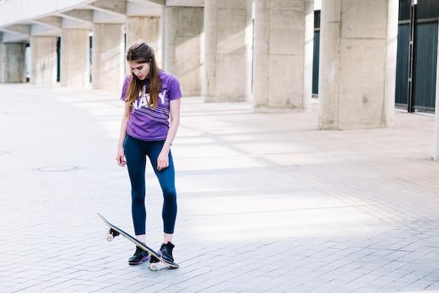Dziewczyna opiera stopę na jej deskorolce