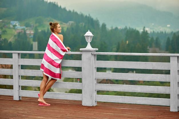Dziewczyna opierała się na poręczy na tarasie i cieszyła się scenerią.