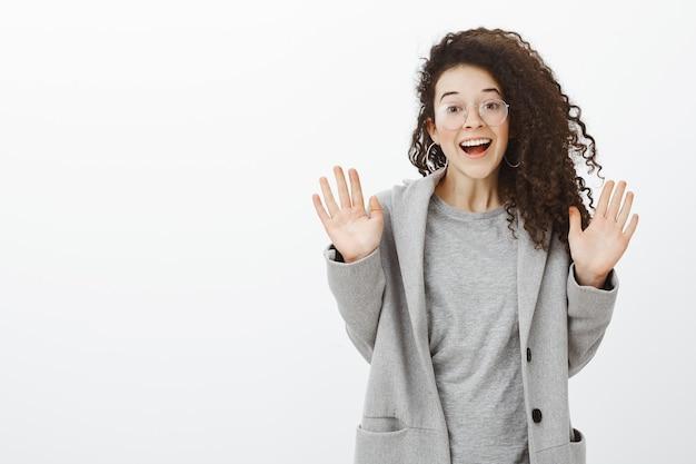 Dziewczyna oszołomiona wspaniałą wiadomością od bestii. portret zadowolonej europejki z kręconymi włosami w okularach i szarym płaszczu, podnosząca dłonie i uśmiechająca się ze szczęścia
