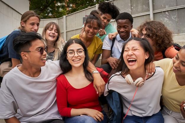 Dziewczyna otoczona przez kolegów z klasy patrząca na uśmiechniętą kamerę szczęśliwi uczniowie w liceum