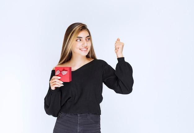 Dziewczyna otrzymała czerwone pudełko i poczuła się szczęśliwa. zdjęcie wysokiej jakości