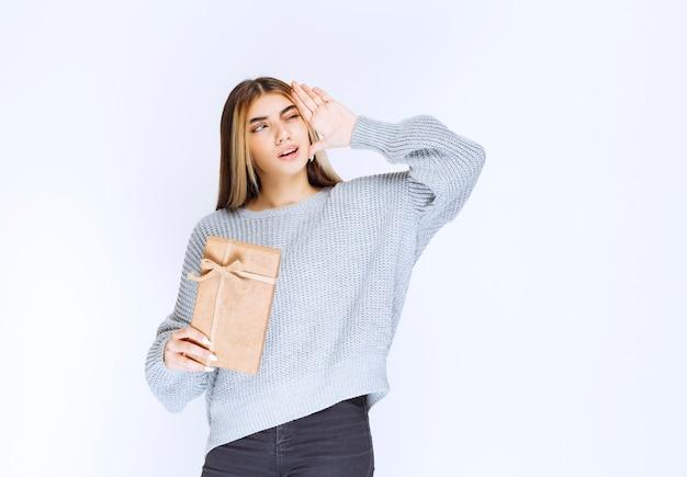 Dziewczyna otrzymała kartonowe pudełko upominkowe od nieznanego nadawcy i zamyśliła się.