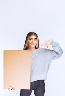 Dziewczyna otrzymała swoje zamówienie w dużym kartonowym opakowaniu.