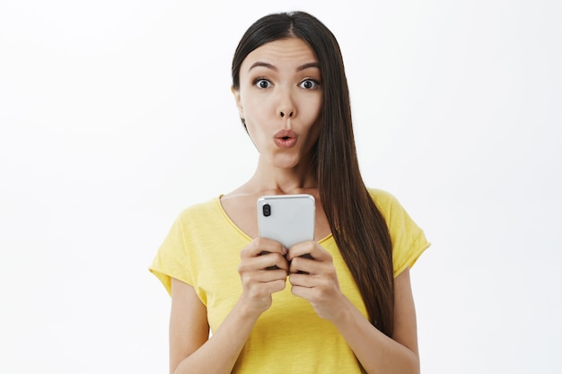 Dziewczyna otrzymująca intrygującą ofertę za pośrednictwem wiadomości składającej usta i wpatrującej się w dźwięk wow