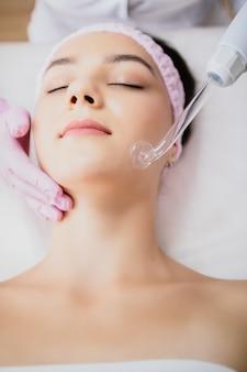 Dziewczyna otrzymująca masaż elektryczny metodą darsonval w gabinecie kosmetycznym