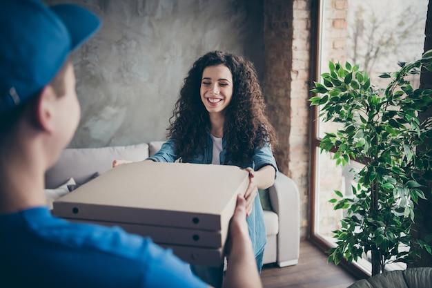Dziewczyna otrzymująca smaczną pyszną pyszną świeżą pizzę w pudełkach w nowoczesnym loftowym pokoju w stylu industrialnym