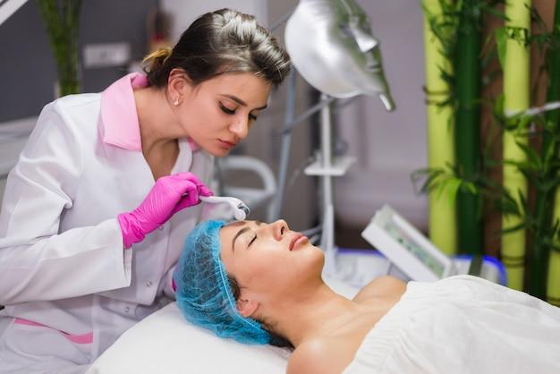 Dziewczyna otrzymywa twarzowego traktowanie w piękno salonie