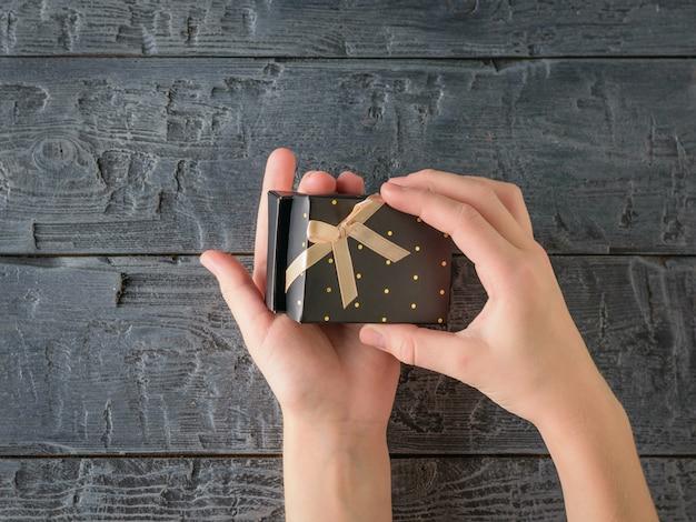 Dziewczyna otwiera czarne pudełko z niespodzianką na czarnym drewnianym stole. widok z góry.