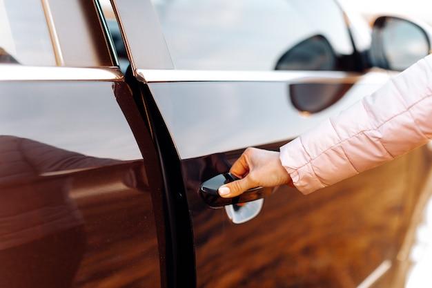 Dziewczyna otwiera drzwi samochodu