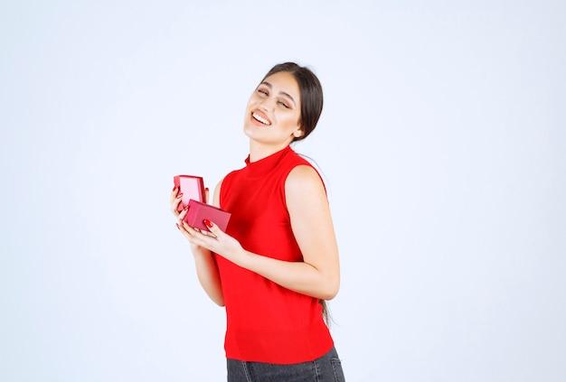 Dziewczyna otworzyła czerwone pudełko i czuje się szczęśliwa.
