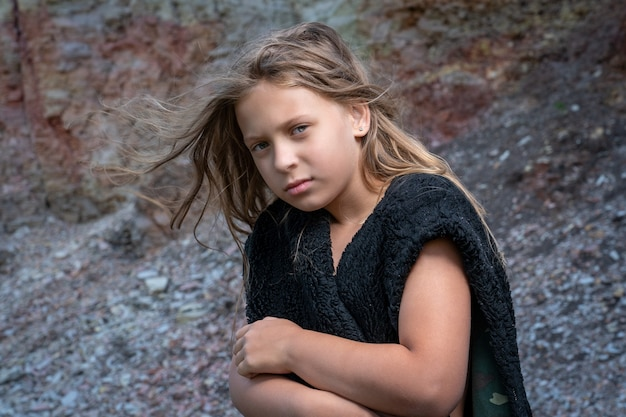 Dziewczyna owija się w futrzaną kurtkę bez rękawów, starając się ogrzać w chłodne dni