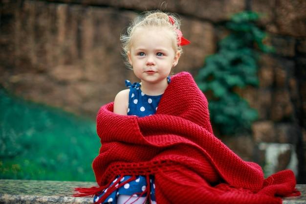 Dziewczyna owinięta czerwonym wełnianym kocem