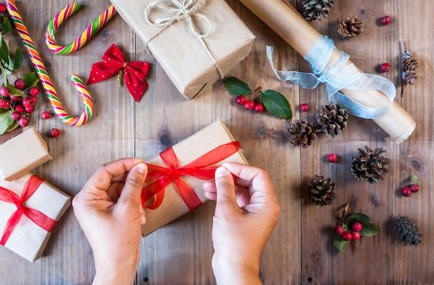 Dziewczyna ozdabia świąteczny prezent, wiąże czerwoną kokardkę.