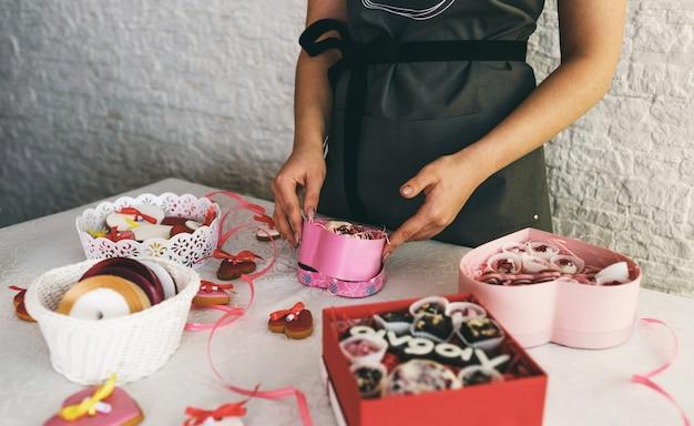 Dziewczyna pakuje ciasta w kolorowe pudełka prezentowe. przygotowanie do uroczystości