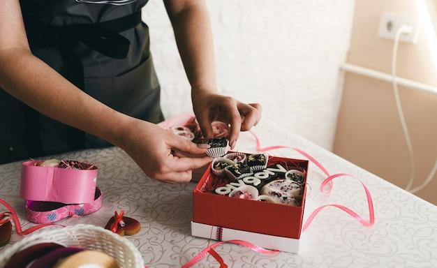 Dziewczyna pakuje ciasta w kolorowe pudełka prezentowe.
