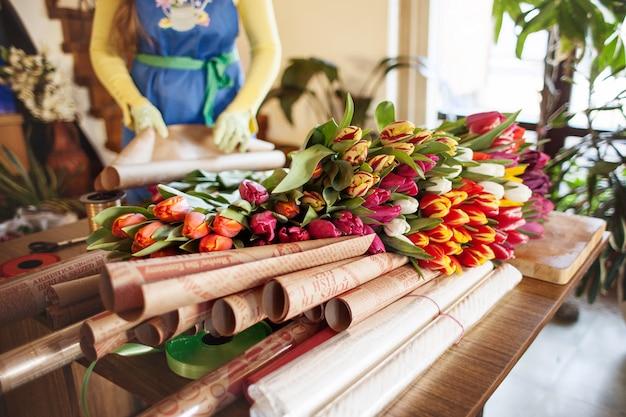 Dziewczyna pakuje kolorowe bukiety tulipanów w papier rzemieślniczy