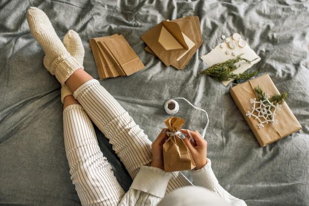 Dziewczyna pakuje prezenty z dekoracją świąteczną