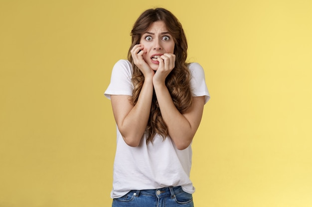 Dziewczyna panikuje uczucie przestraszony nieśmiały niepewny obgryzanie paznokcie patrzenie na aparat przestraszony zaciska zęby drżenie strach dotyk twarz nerwowo uczucie niepewność przestraszony stoisko żółte tło