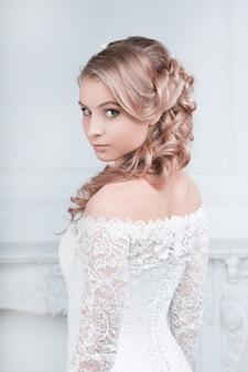 Dziewczyna panna młoda w sukni ślubnej w pięknej stylowej fryzurze
