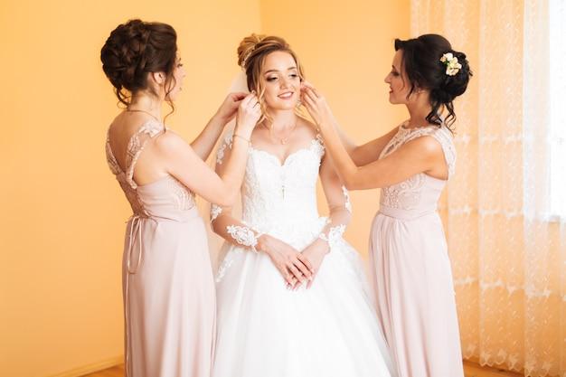 Dziewczyna panny młodej przygotowuje pannę młodą na dzień ślubu. dziewczyna panny młodej pomaga zabezpieczyć suknię ślubną panny młodej przed ceremonią