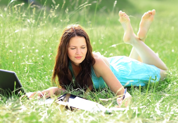 Dziewczyna park pisze laptop na papierze