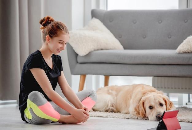 Dziewczyna patrząc na tablet i uśmiech podczas treningu jogi online, a piesek golden retriever leży blisko niej