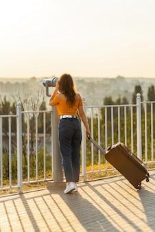 Dziewczyna patrząc przez lornetkę w parku, trzymając walizkę