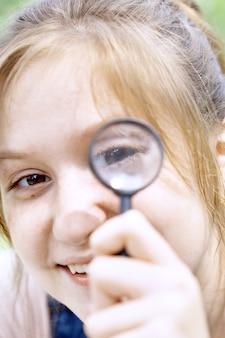 Dziewczyna patrząca przez szkło powiększające