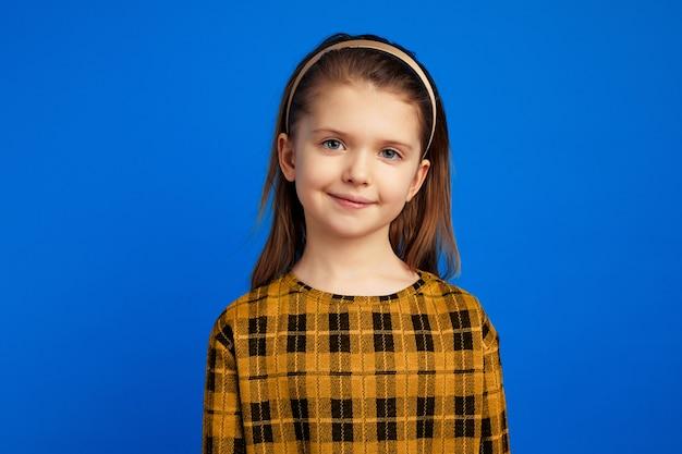 Dziewczyna patrząca spokojnie i stojąca odizolowana nad niebieską ścianą
